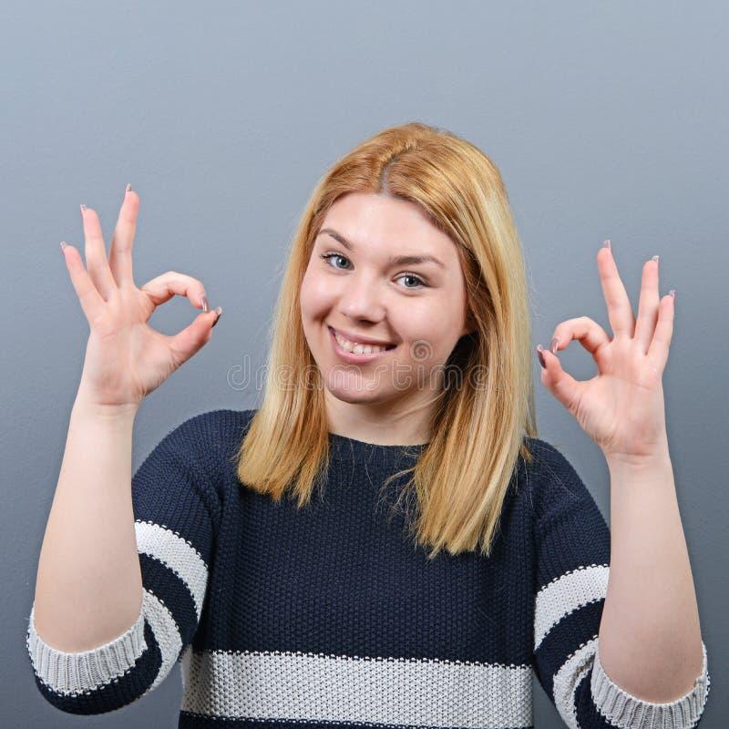 Porträt des okayzeichens der glücklichen Frauenvertretung gegen grauen Hintergrund stockfoto