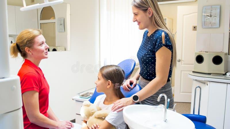 Porträt des pädiatrischen Zahnarztes zur jungen Mutter des kleinen Patienten lizenzfreie stockfotos