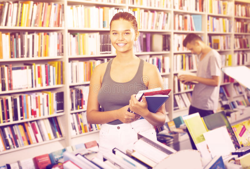 Porträt des positiven Mädchenjugendlichen, der neue Bücher hält stockfoto