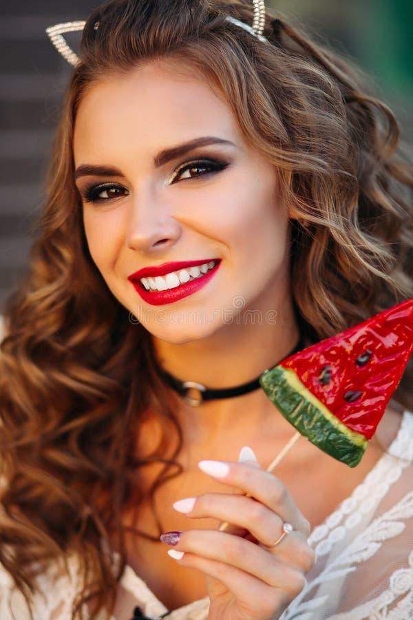 Porträt des positiven sexy Brunette mit den roten Lippen, die Süßigkeit halten lizenzfreie stockfotografie