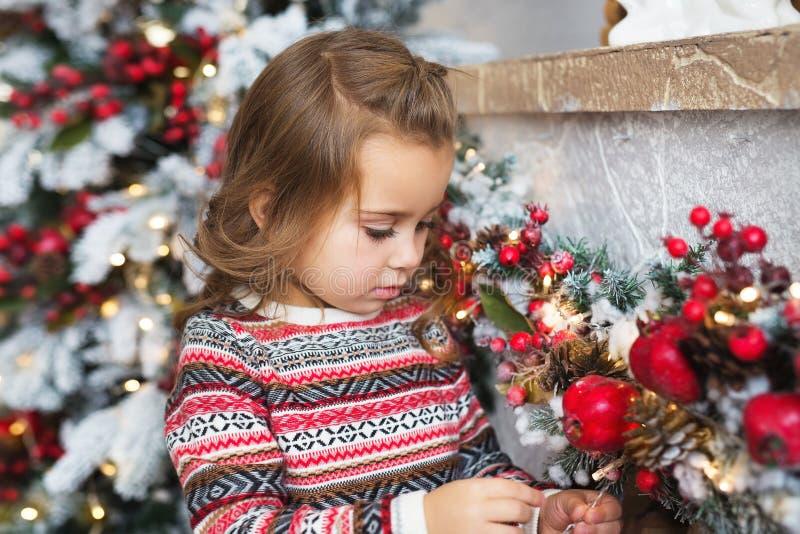 Porträt des recht kleinen Mädchens betrachtet ein Weihnachtsspielzeug zu Hause stockbilder