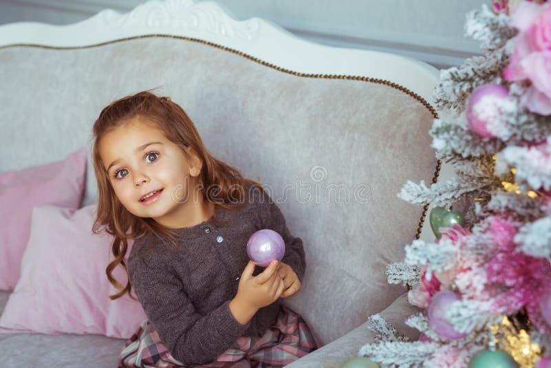 Porträt des recht kleinen Mädchens hält ein Weihnachtsspielzeug zur Hand auf einem Sofa nahe Weihnachtsbaum lizenzfreie stockfotografie