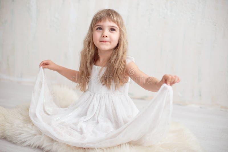 Porträt des recht kleinen Mädchens im weißen Kleid, die Kamera und Lächeln betrachtend und stehen gegen grauen Hintergrund lizenzfreie stockbilder