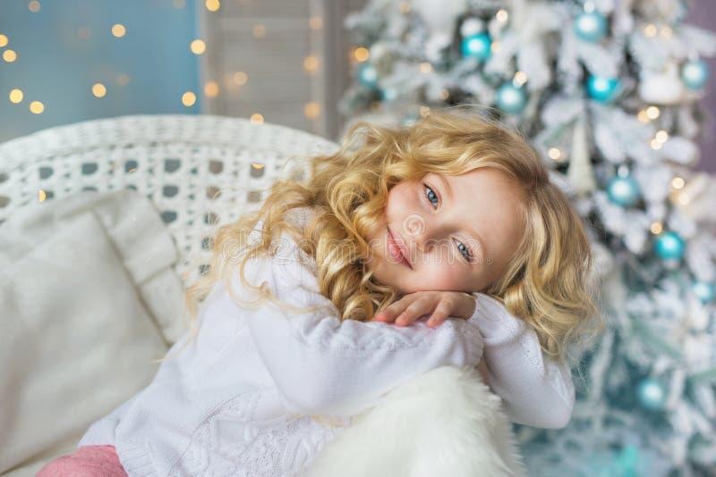 Porträt des recht kleinen Mädchens sitzt und träumt auf einem Stuhl in der Weihnachtszeit stockbild