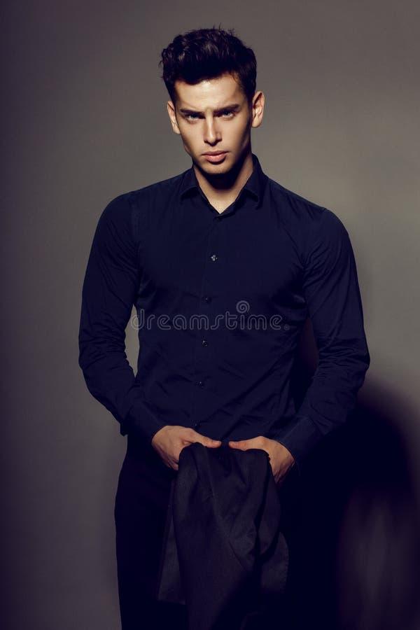Porträt des reichen, sexy brunette Mannes im schwarzen Anzug, der auf der Kamera, lokalisiert auf grauem Hintergrund aufwirft lizenzfreie stockfotografie