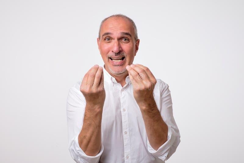 Porträt des reifen gutaussehenden Mannes im weißen Hemd, das italienische Geste zeigt lizenzfreies stockbild