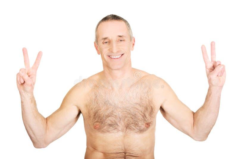 Porträt des reifen hemdlosen Mannes mit Siegeszeichen lizenzfreie stockfotografie
