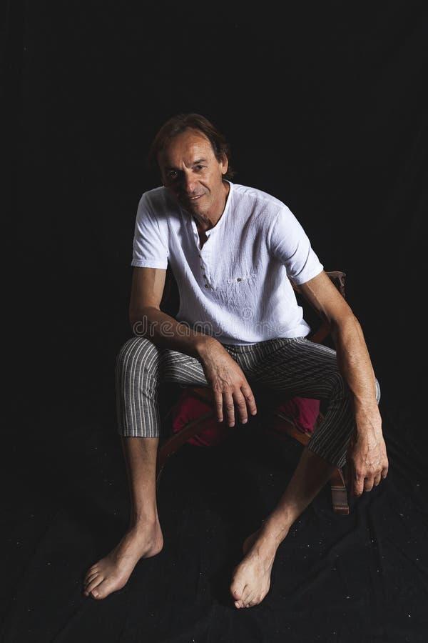 Porträt des reifen Hippie-Mannes, der in einem Fotostudio sitzt lizenzfreie stockfotografie