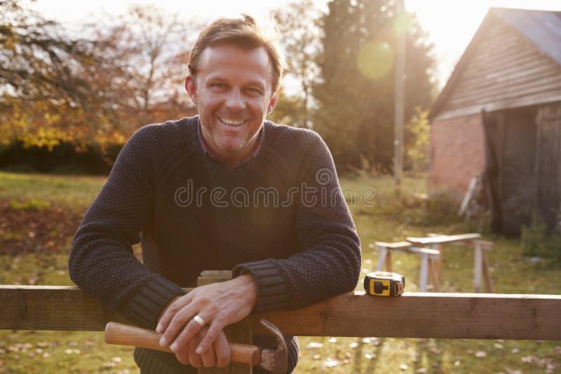 Porträt des reifen Mannes Garten-Zaun reparierend stockfotografie