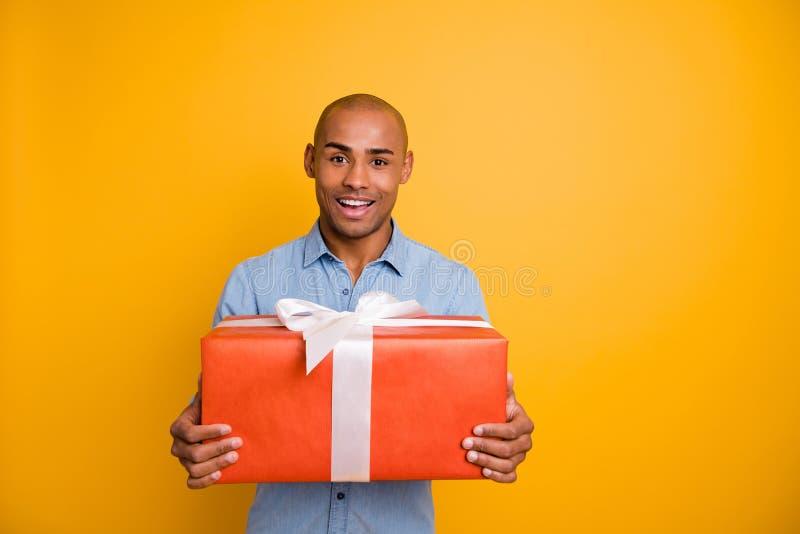 Porträt des reizend Kerlgriff-Handgeschenks am 14. Februar am 8. März zufriedenes glauben lokalisiert über gelbem Hintergrund lizenzfreie stockfotografie