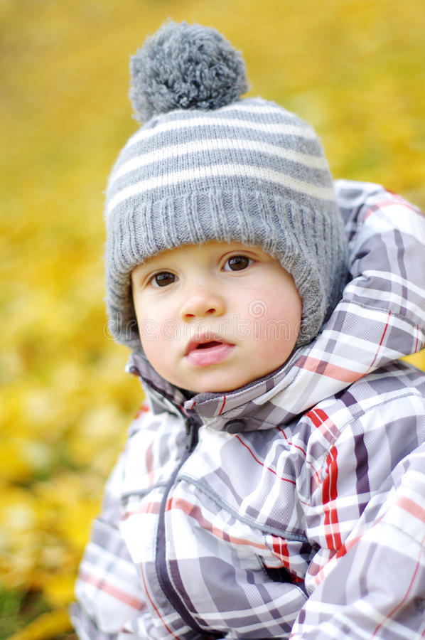 Porträt des reizenden Babys draußen im Herbst gegen gelbes Le stockfotografie