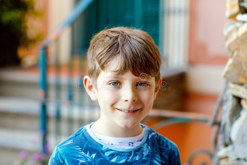 Porträt des reizenden gorgeos Schulkinderjungen, der vor Haus sitzt Glücklicher gesunder Junge auf Treppe durch Haus stockfotografie