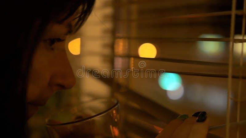 Porträt des romantischen glücklichen Mädchens mit Tasse Kaffee oder Tee sitzen nahe dunklem Nachtfenster Ansicht über Stadtstadt  stockfotos