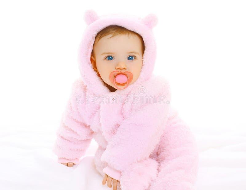 Porträt des süßen Babys mit Friedensstifter im weichen Overall stockfotografie