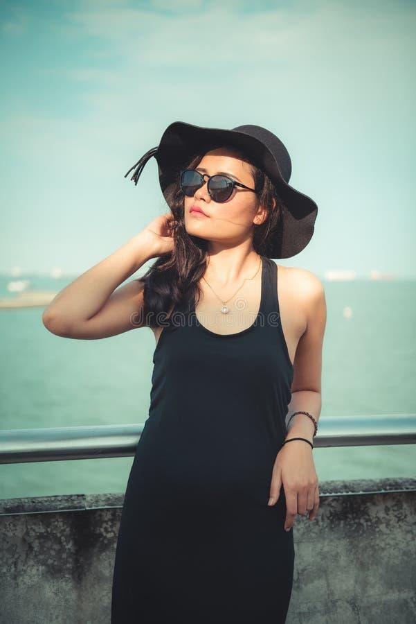 Porträt des schönen Asiatin-in Mode schwarzen Kleides mit ihrem Hut auf Ufergegend-Hintergrund, Schönheit und Mode-Konzept lizenzfreie stockfotografie