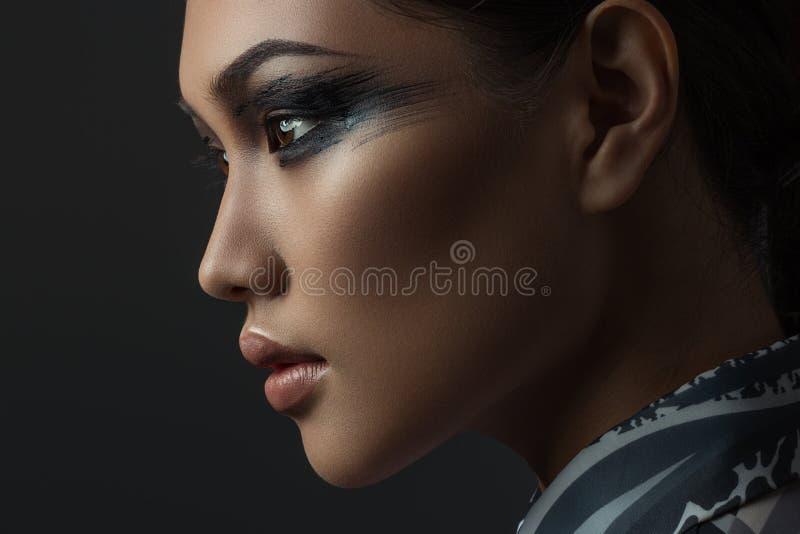 Porträt des schönen asiatischen Mädchens mit kreativem Kunstmake-up Stellen Sie eingelassen dem Studio auf einem schwarzen Hinter lizenzfreie stockfotografie