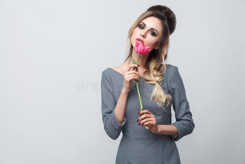 Porträt des schönen attraktiven Mode-Modells im grauen Kleid mit Make-up und Frisur, stehend, halten rote Tulpe und betrachten stockfoto