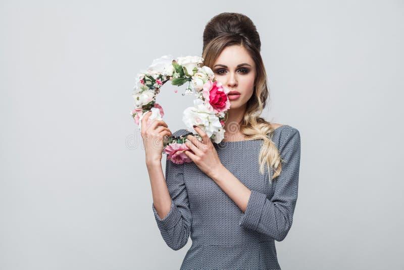 Porträt des schönen attraktiven Mode-Modells im grauen Kleid mit Make-up und Frisurstellung, Hauptblume und das Schauen halten lizenzfreies stockbild