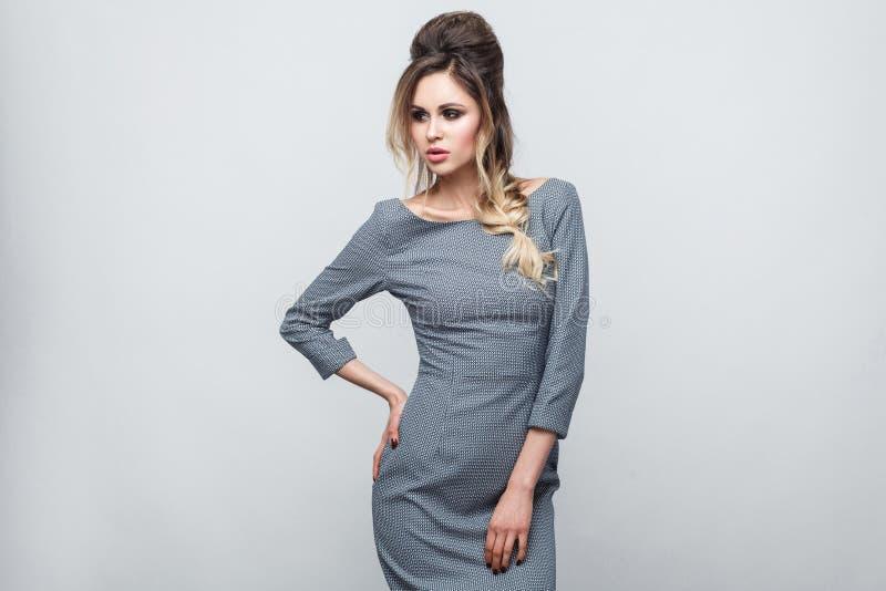 Porträt des schönen attraktiven Mode-Modells im grauen Kleid mit Make-up und Frisurstellung, werfend mit der Hand auf Taille auf  lizenzfreie stockfotografie