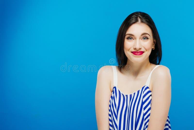 Porträt des schönen Brunette im gestreiften Sommer-Kleid, das im Studio auf blauem Hintergrund aufwirft lizenzfreies stockbild