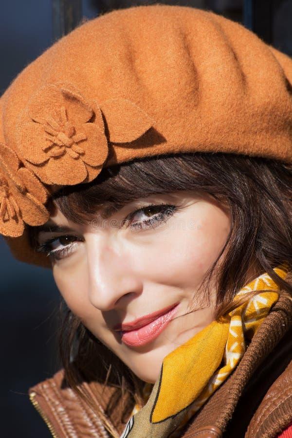 Porträt des schönen Brunette mit der braunen Kappe stockfotografie