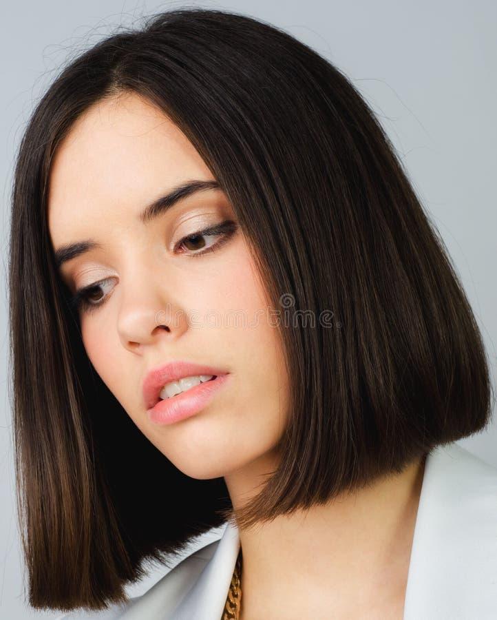 Porträt des schönen Brunettemädchens lokalisiert auf grauem Hintergrund lizenzfreies stockbild