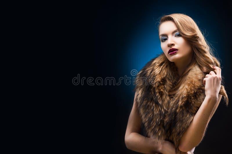 Porträt des schönen eleganten Mädchens, das einen Pelzwaschbärkragen trägt lizenzfreie stockbilder