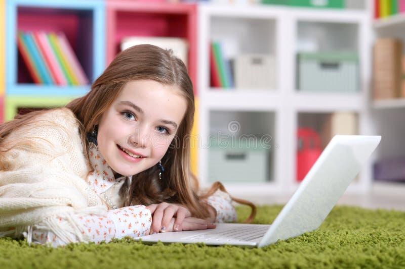 Porträt des schönen emotionalen netten Mädchens, das Laptop verwendet lizenzfreie stockfotografie