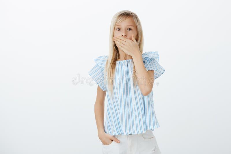 Porträt des schönen entsetzten Mädchens mit dem blonden Haar in der blauen Bluse, Keuchen, Mund bedeckend, um nicht von der Furch lizenzfreie stockfotos
