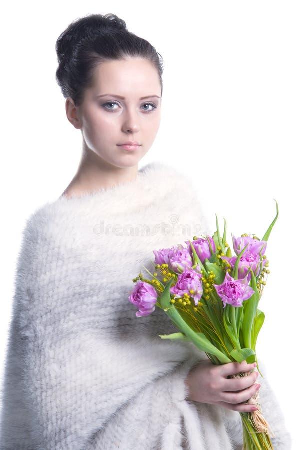 Schönheitsfrau im warmen weißen woolen Poncho mit Frühling blüht in ihren Händen lizenzfreies stockfoto