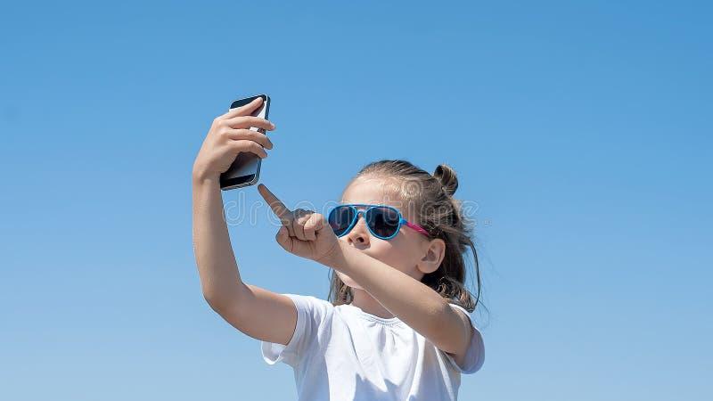 Porträt des schönen glücklichen kleinen Mädchens, das ein selfie am Kameratelefon mit blauem Himmel auf Hintergrund nimmt Junges  stockbild