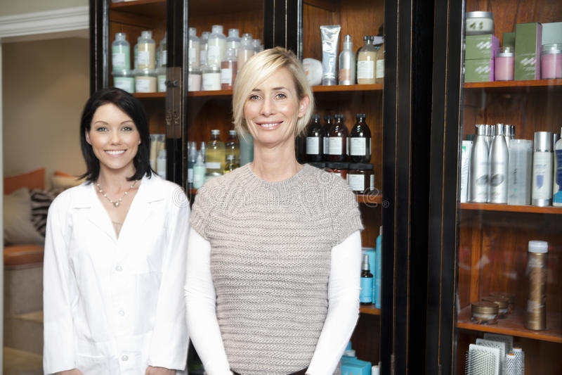 Porträt des schönen Inhabers mit dem Angestellten, der vor kosmetischen Produkten steht lizenzfreie stockfotos
