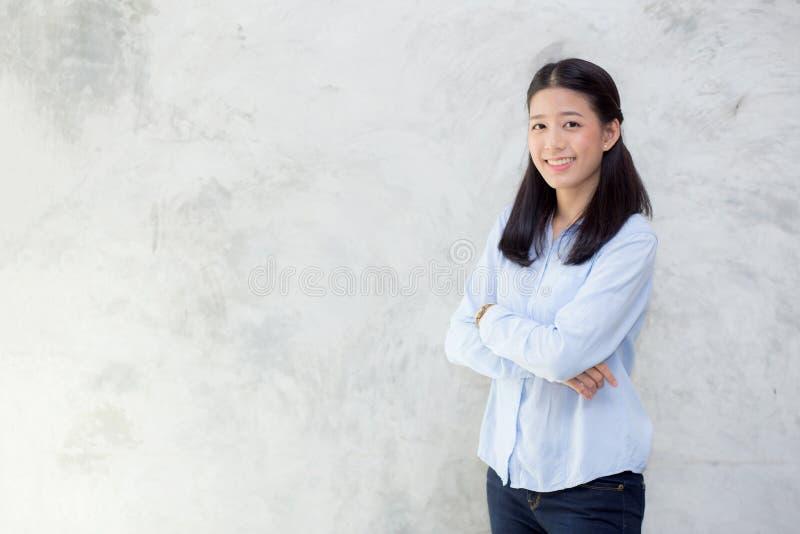 Porträt des schönen jungen asiatischen Frauenglückes, das auf grauem Zementbeschaffenheitsschmutz-Wandhintergrund steht lizenzfreie stockbilder