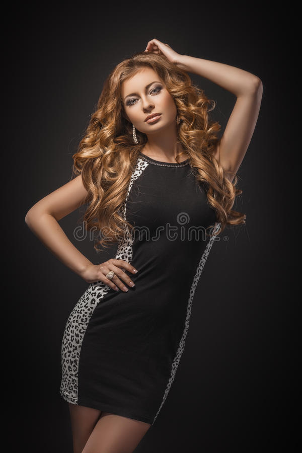 Porträt des schönen jungen blonden Mädchens im schwarzen Kleid lizenzfreie stockbilder