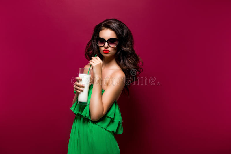 Porträt des schönen jungen Brunette in der Sonnenbrille und im grünen dre stockfotografie