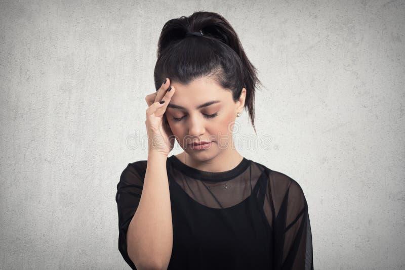 Porträt des schönen jungen Brunette mit den bloßen Schultern, die ihre Tempel glauben Druck, auf grauem Hintergrund berühren stockfotos