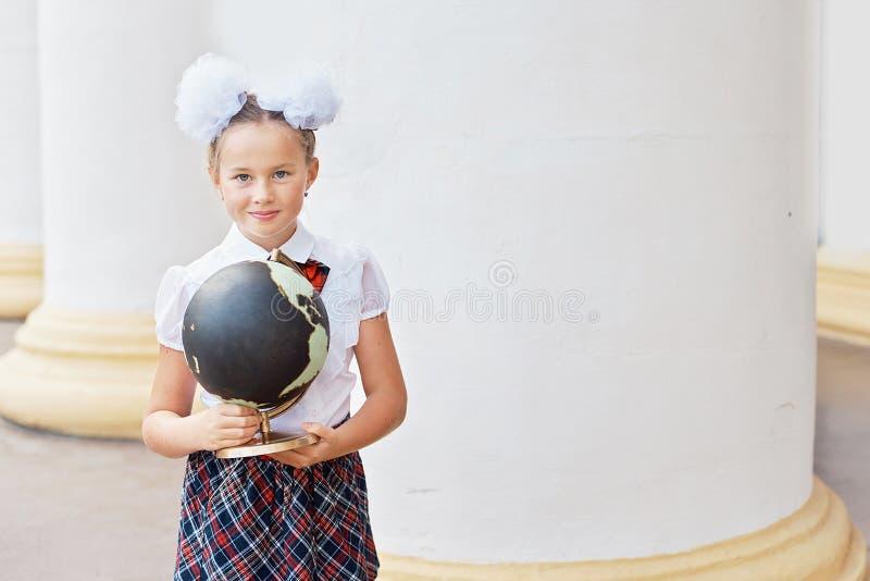 Porträt des schönen jungen Erstsortierers Abschieds-Bell Tag des Wissens Beginn des neuen Schuljahres Schulausrüstung jung lizenzfreies stockbild