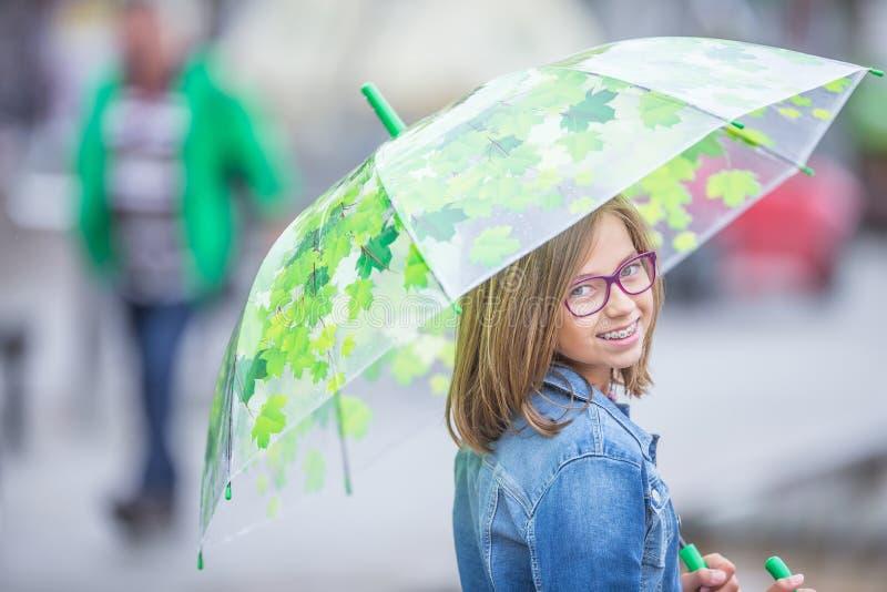 Porträt des schönen jungen jugendlichen Mädchens mit Regenschirm unter SP stockfotografie