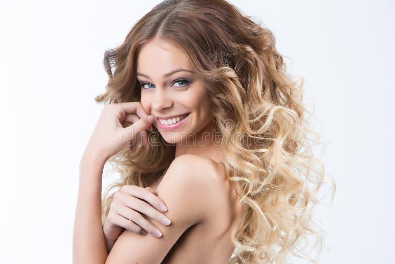 Porträt des schönen jungen lächelnden Mädchens mit dem luxuriösen Haarwinden Gesundheit und Schönheit lizenzfreies stockfoto