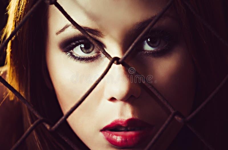 Porträt des schönen jungen Mädchens hinter dem metallischen Gitter. Nahaufnahme stockfotos