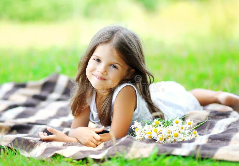 Porträt des schönen Kindes des kleinen Mädchens mit Kamille blüht stockfotografie