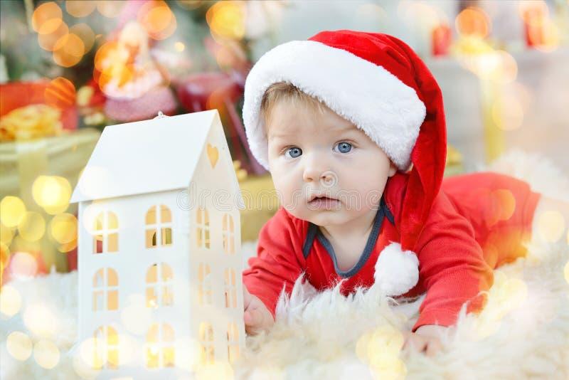 Porträt des schönen kleinen Babys feiert Weihnachten Neues Jahr ` s Feiertage Junge in einem Sankt-Kostüm mit Spielzeughaus unter stockbild