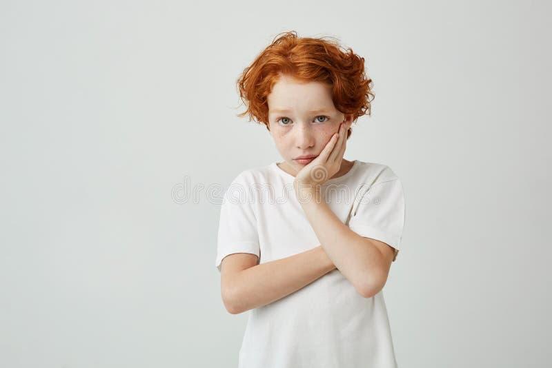 Porträt des schönen kleinen Kindes mit dem roten Haar und den Sommersprossen halten Haupt mit der Hand, Mutter mit schuldigem bet lizenzfreie stockfotos