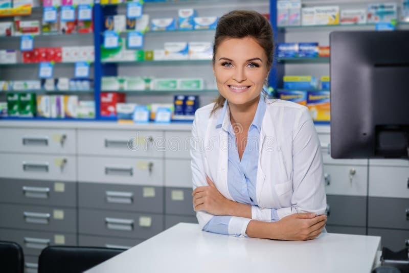 Porträt des schönen lächelnden Apothekers der jungen Frau, der in der Apotheke steht stockfoto