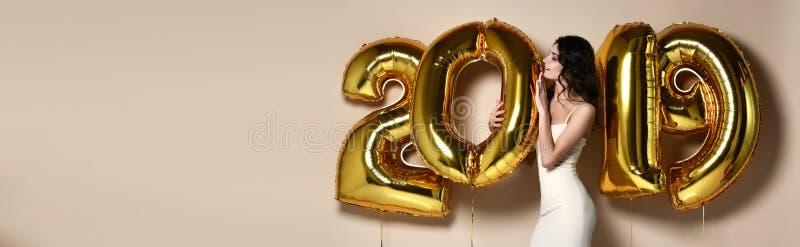 Porträt des schönen lächelnden Mädchens in glänzendes goldenes Kleiderwerfenden Konfettis, Spaß mit Gold habend 2018 Ballone auf  stockfoto