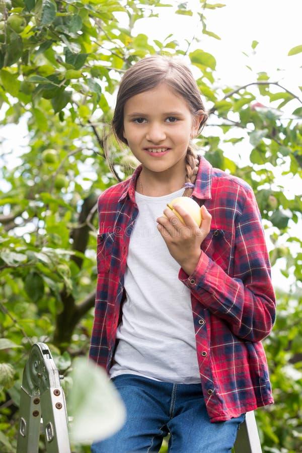 Porträt des schönen lächelnden Mädchens im karierten Hemd, das herein aufwirft stockfotografie