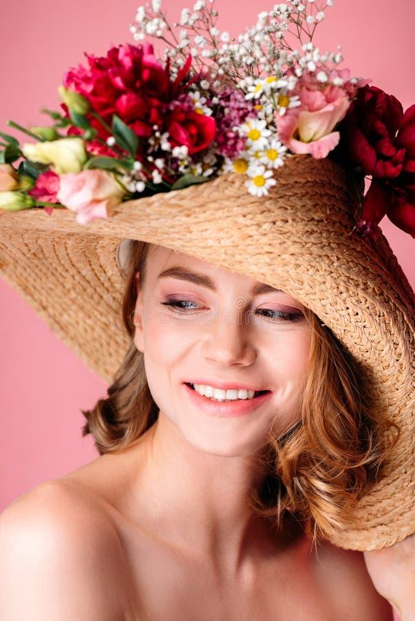 Porträt des schönen lächelnden nackten Mädchens, das Weidenhut mit Blumen trägt lizenzfreies stockbild