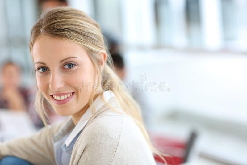 Porträt des schönen lächelnden Studenten, welche an Klasse teilnimmt stockbild