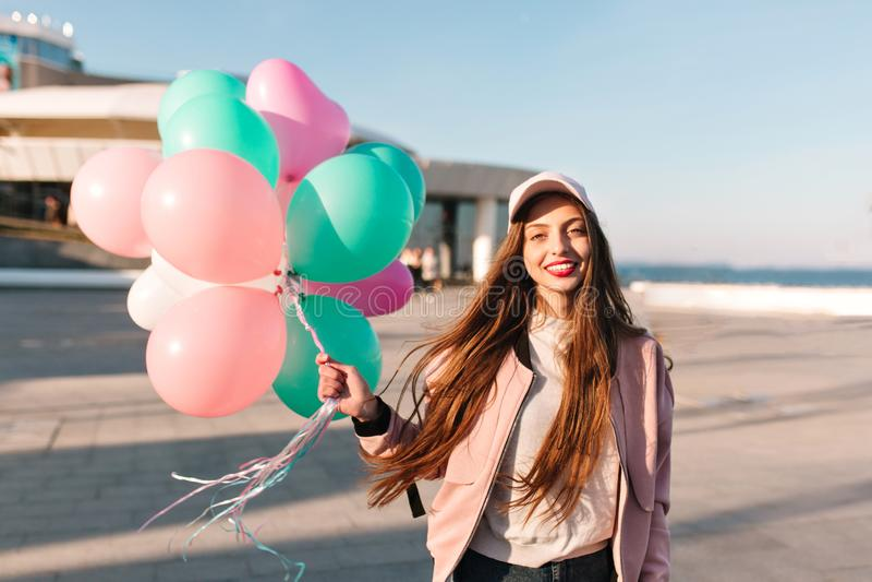 Porträt des schönen langhaarigen brunette Mädchens, das am Seepier während Wind wellenartig bewegt ihr Haar aufwirft Entz?ckende  lizenzfreies stockfoto