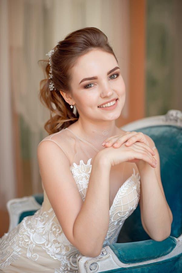 Porträt des schönen luxuriösen weiblichen Modells mit dem Mittelbraunhaar in einem langen fashinable Kleid, das im Raum steht stockfoto